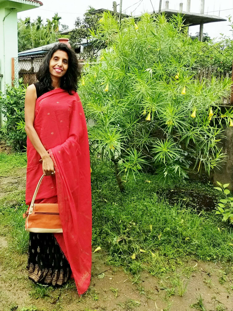 Creation of a saree look by adding a red printed dupatta and a black pleated skirt with print image